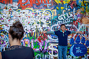 Tourist visiting The Lennon Wall or John Lennon Wall, which is a wall in Prague, Czech Republic. Once a normal wall, since the 1980s it has been filled with John Lennon-inspired graffiti and pieces of lyrics from Beatles songs.