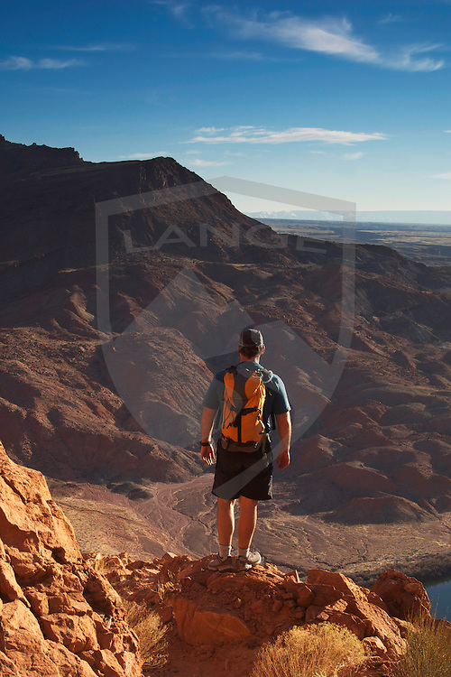 nature scenery and outdoor recreation and adventure: man hiker with backpack overlooking the southwest desert mountain landscape at lee's ferry, grand canyon, arizona, usa, vertical, space for text