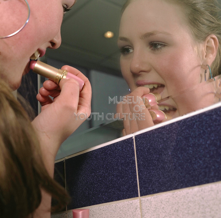 Girl putting on lip stick in front of the mirror, Cardiff 2000's