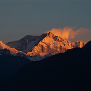 "Kangchenjunga - the world's third highest peak, whose name means ""Five Treasure Houses of Snow"" - glows at sunset from the village of Pelling, West Sikkim, India."