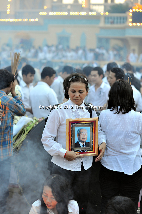 A mourner holds up a photo of King Father Norodom Sihanouk while waiting at the Royal Palace for his body to return to Phnom Penh, starting a week of mourning in Cambodia.