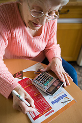 Older woman filling in details of outgoings to work out a weekly budget,