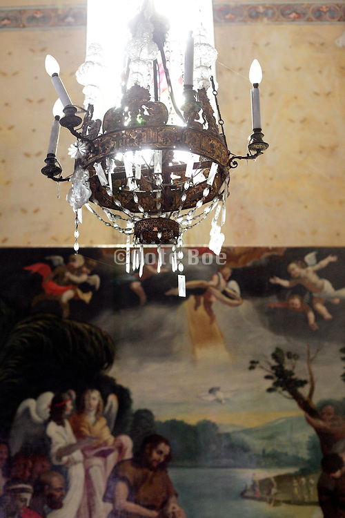 religious painting with window light and chandelier