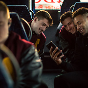 Loyola University Chicago basketball teammates watch videos on their phones while headed to O'Hare International Airport for the NCAA Tournament in Dallas, TX., early on Tuesday morning, March 13, 2018. (Photo: Lukas Keapproth)