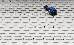 London, 03 August 2017. A stadium worker cleans one of 60,000 seats ahead of the IAAF World Championships London 2017 at the London Stadium.
