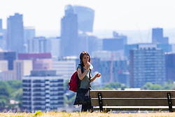 A woman on Parliament Hill takes a sip of water on another hot day in London. London, July 03 2018.