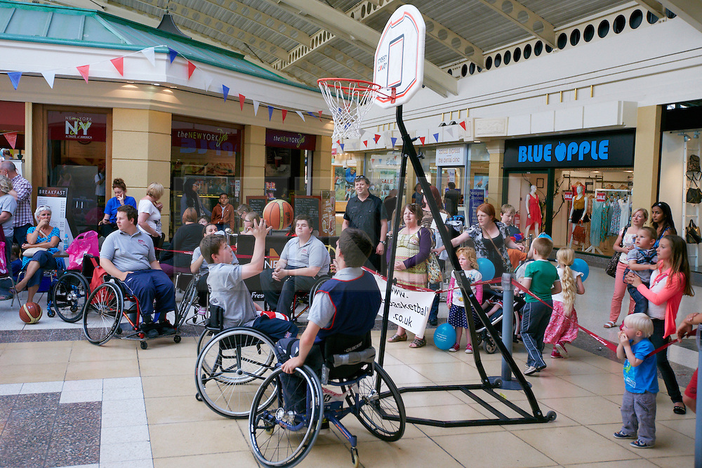 © Licensed to London News Pictures.  28/08/2012. AYLESBURY, UK. Disabled and able bodied children try out wheel chair basketball during a paralympic flame celebration in Aylesbury town centre. Nearby Stoke Mandeville is the birthplace of the paralympics and a 24 hour torch relay began at 8pm this evening (Tuesday) and will finish in the Olympic Park in Stratford tomorrow. Photo credit :  Cliff Hide/LNP