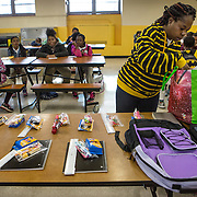 WASHINGTON, DC - APR 24:  Simon Elementary school parent Layana Campbell, volunteers setting up the raffle prizes in the cafeteria at Simon Elementary School in Washington, DC, April 24, 2014. DC has enormous truancy rates, even among young children. In the last year or two, the school system has made a big push to improve attendance. Simon Elementary is seen as a model, introducing incentives and games that are tied to attendance and meant to get kids excited about coming to school; systems to ensure that parents get a call home whenever their kids are absent; weekly attendance meetings to talk about kids who are missing too much school; and a partnership with a community based organisation that can make home visits and connect families with services. (Photo by Evelyn Hockstein/For The Washington Post)
