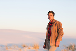 good looking man outdoors in a coat at sunset