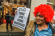 """The Out and Proud Diamond Group and the Peter Tatchell Foundation support the international boycott of Dolce and Gabbana and lead a protest outside their flagship London store, 6-8 Old Bond Street, London 19 March 2015. The protest is in response to the fashion designers 'insulting slurs' against same-sex parents and their children. Speaking to the Italian magazine Panorama, alongside his business partner, Stefano Gabbana, Domenico Dolce said children should be born to a mother and a father: """"The only family is a traditional one. I'm not convinced by those I call the chemical children, synthetic babies...They are wombs for hire, semen chosen from a catalogue ... psychiatrists are not ready to confront the effects of this experimentation."""" Stefano Gabbana added: """"The family is not a fad."""" In 2006, he told the Daily Mail: """"I am opposed to the idea of a child growing up with two gay parents."""""""