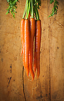 Studio still lifes of a bunch of carrots in front of a wood background.