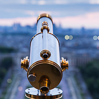 France, Paris, Tourists' viewing telescope at top of 324 meter tall Eiffel Tower at dusk on spring evening