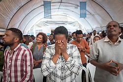 27 October 2019, Addis Ababa, Ethiopia: A woman covers her face in prayer during Sunday service at the Finfinne Oromo Mekane Yesus Congregation of the Ethiopian Evangelical Church Mekane Yesus. In a context where congregations did not use to be allowed to hold their services in any language but Amharic, the congregation today is one of some 60 Oromo speaking Mekane Yesus congregations in Addis Ababa. The service takes place on the first Sunday following political turmoil in the country, claiming dozens of lives.