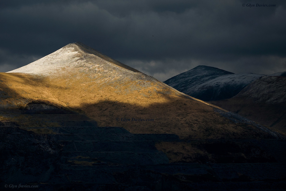 Subtle washes of sunlight permeate the winter gloom and illuminate isolated sections of this ancient Welsh landscape. Elidir Fawr becomes a snow-capped volcano and Y Garn sits solemnly in the shadows behind. A single crow flies across the void between me and the distant peaks, its call echoing sharply in the valley below.