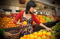 Young woman selecting oranges in farmer's market
