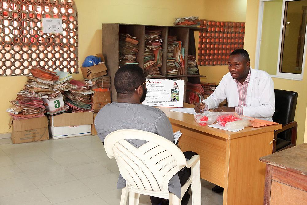 INDIVIDUAL(S) PHOTOGRAPHED: N/A (left) and Dr. Ogundimu Opeyemi (right). LOCATION: Lagos State University Teaching Hospital Dot Clinic, Lagos, Nigeria. CAPTION: A staff member explains to a patient how to prevent tuberculosis using an informative flipbook.