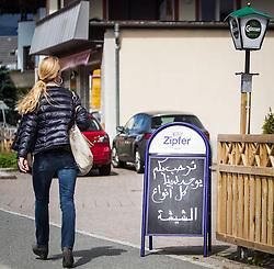 THEMENBILD, ARABISCHE TOURISTEN IN ZELL AM SEE - KAPRUN, im Bild eine Einheimische Frau spaziert bei einem Restaurant-Schild in arabischer Sprache geschrieben vorbei. Jedes Jahr besuchen mehrere Tausend Gäste aus dem arabischen Raum die Urlaubsregion im Salzburger Pinzgau. Um Missverständnisse zu vermeiden und die Gäste auf den Aufenthalt vorzubereiten, erhalten die Touristen einen Knigge-ähnlichen Kulturführer, aufgenommen am 30.05.2014 in Kaprun, Österreich // ILLUSTRATION, ARAB TOURISTS IN ZELL AM SEE - KAPRUN, pictured: a local woman walks trough a restaurant sign in Arabic letters. Every year thousands of guests from Arab countries takes their holiday in Zell am See - Kaprun Region. To avoid misunderstandings and to prepare the guests for their holidays, the tourists get a similar etiquette culture guide, Kaprun, Austria on 2014/05/30. EXPA Pictures © 2014, PhotoCredit: EXPA/ JFK