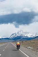 Cyclist biking toward El Chalten and the impressive FizRoy mountain massif, Argentina