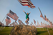 Helleney Avila, 9, jumps off from the top of a rock amongst 3,000 US flags are displayed at Pepperdine University to mark the 12th anniversary of the 9/11 terror attack, September 10, 2013 in Malibu, California. Photo by Ringo Chiu/PHOTOFORMULA.com)