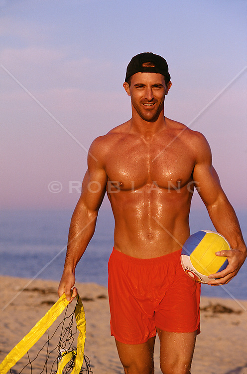 sexy volleyball player at the beach with a ball and net in hand