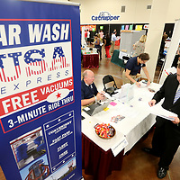 Job hunter Eric Griffith, of Amory, leaves the Car Wash USA Express job booth, to fill out applications after meeting with Dan Echlin, Regional Director of Operations, and Marilyn Swindle, Human Resource Specialist, during the Mega Job Fair on Tuesday that was held in Building V of the Tupelo Furniture Market.