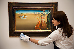 © Licensed to London News Pictures. 01/02/2012. LONDON, UK. A member of Sotherby's staff cleans 'Oasis' by Salvador Dali, ahead of an auction of Impressionist and Modern Art held on the 8th of February 2012. The piece is estimated to raise £4,000,000-6,000,000. Photo credit: Matt Cetti-Roberts/LNP