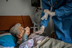 Milan. USCA Special Home Guard Medical Units ATS and General Practitioners to Help Patients at home infected with COVID19 Coronavirus while assisting an 88-year-old lady