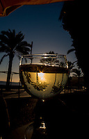 A glass of white wine in the sunset on a pavement restaurant in Sismbra, Portugal