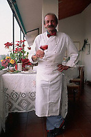 June 1992, Albaretto della Torre, Italy --- Chef Cesare Gioccone Holding Glass of Wine --- Image by © Owen Franken/CORBIS