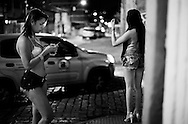 "Lara Santos and Karol. Lara exchange messages with a client while Karol waves to a car. In Campinas the dress code requires showing more body, unlike what happens in São Paulo. To ""meet"" clients in this street, they must pay a commission to a woman who runs it."