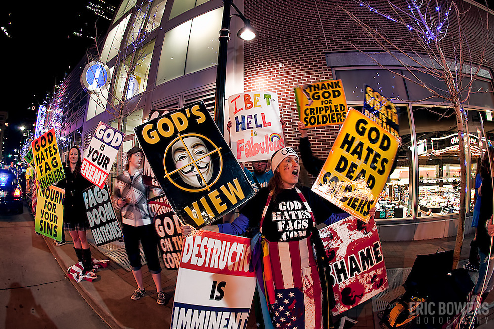 The anti-gay Westboro Baptist Church stages a protest in response to a screening of the film Red State at the Midland Theatre in Kansas City, MO. In this shot one of the counter protesters snuck in behind the woman in front to hold his own sign.