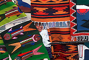 ECUADOR, MARKETS, CRAFT Otavalo Market; girl and woven textiles