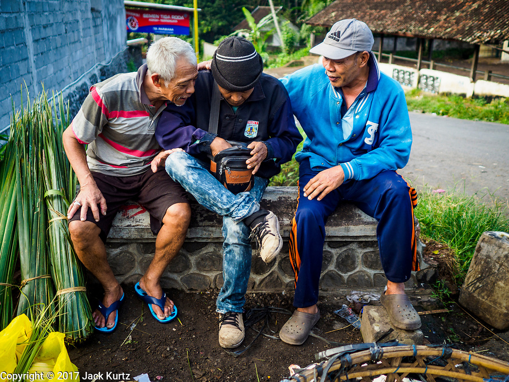07 AUGUST 2017 - BEBANDEM, BALI, INDONESIA:  Men socialize in the market in Bebandem, in far eastern Bali. The market is known for baskets, which are woven in the area. Bali's local markets are open on an every three day rotating schedule because venders travel from town to town. Before modern refrigeration and convenience stores became common place on Bali, markets were thriving community gatherings. Fewer people shop at markets now as more and more consumers go to convenience stores and more families have refrigerators.    PHOTO BY JACK KURTZ