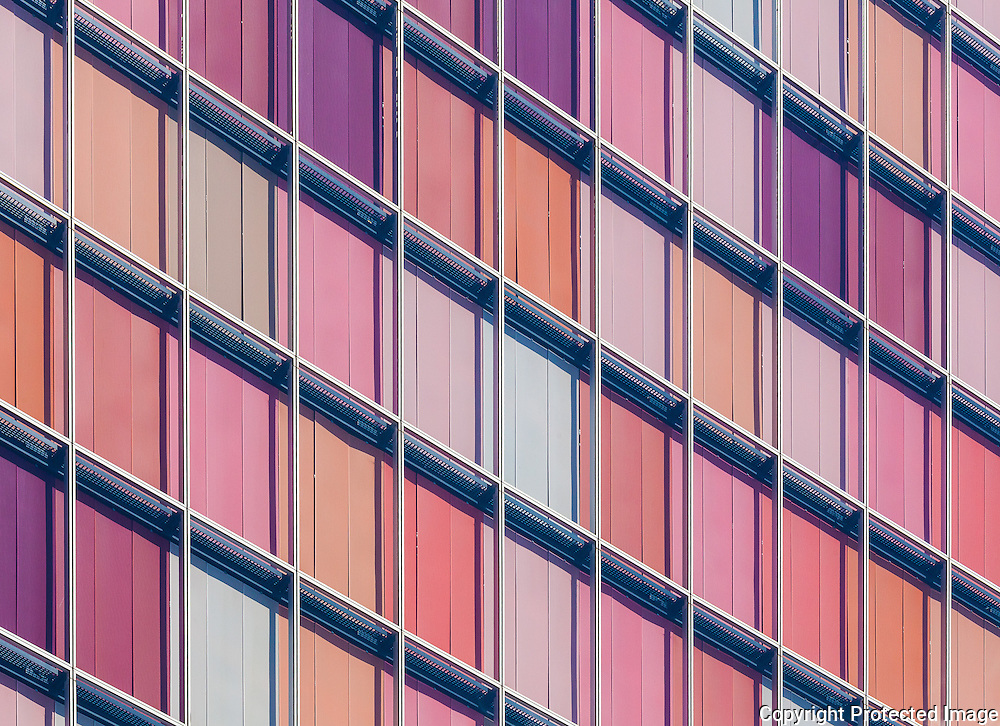 GSW Headquarters, Berlin, Germany. The windows are polychromatic pastel hues of orange and rose when the window shades are closed. Built 1999. Architect: Sauerbruch Hutton