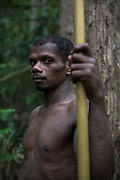 A Maniq man stands for a portrait holding the traditional blow pipe which they still use to hunt for their food.<br /> <br /> Evidence suggests that the Maniq, a Negrito tribe of hunters and gatherers, have inhabited the Malay Peninsula for around 25,000 years. Today a population of approximately 350 maniq remain, marooned on a forest covered mountain range in Southern Thailand. Whilst some have left their traditional life forming small villages, the majority still live the way they have for millennia, moving around the forest following food sources. <br /> <br /> Quiet and reclusive they are little known even in Thailand itself but due to rapid deforestation they are finding it harder to survive on the forest alone and are slowly being forced to move to its peripheries closer to Thai communities.