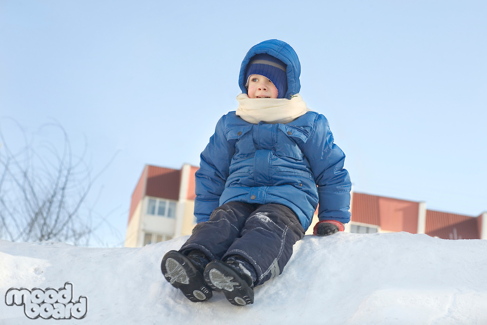 Young boy sitting in the snow