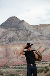 cowboy with a lasso and duffle bag outdoors by a mountain