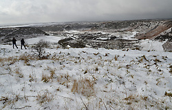 © Licensed to London News Pictures. 15/02/2016. North Yorkshire Moors, UK. Walkers at the Hole of Horcum, North Yorkshire Moors as a snow shower approaches. Photo credit : Anna Gowthorpe/LNP