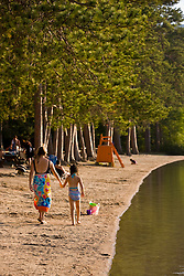 A woman and her daughter walk the beach at White Lake State Park in Tamworth, New Hampshire.