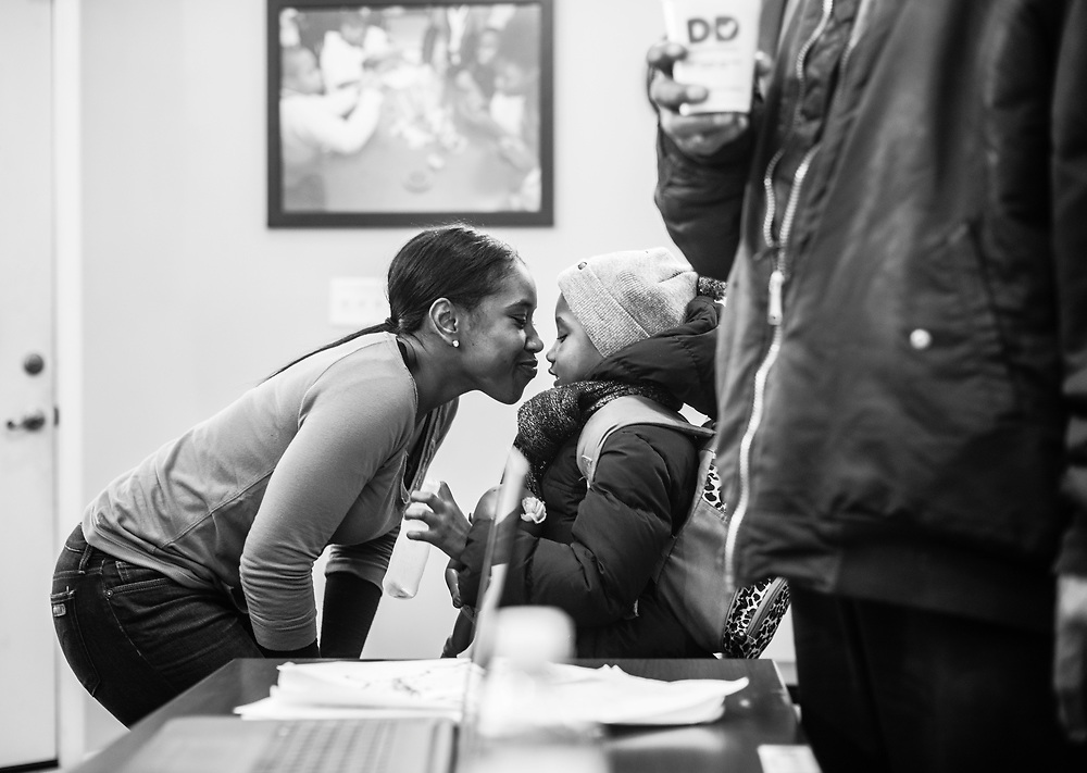 BALTIMORE, MD -- 3/2/16 -- Sharone gives her daughter, Taylor McRae, a kiss as she leaves the SAFE center.  Van and his girlfriend, Sharone McRae, keep things running at the center. Safe Alternatives is more than just an effort by Van. His family is a big part of the project.<br /> Van Brooks runs the Safe Alternative Center, which he started to give middle school kids in West Baltimore a safe place to learn and play. <br /> <br /> Brooks was a Division 1 prospect when he played football in high school, but was paralyzed in a freak accident after making a tackle in his junior year. He regained the use of his arms, even walking again with much assistance, and graduated on time from high school. He later earned a degree in marketing from Towson University. Though still confined to a wheelchair, he is self-sufficient and runs the center.&hellip;by Andr&eacute; Chung #_AC22395