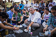 "15 JANUARY 2014 - BANGKOK, THAILAND: SUTHEP THAUGSUBAN, former Deputy Prime Minister of Thailand and leader of the Shutdown Bangkok anti-government protests, eats his lunch in the Ekkamai intersection in Bangkok. The protest march stopped at Ekkamai for a picnic. Tens of thousands of Thai anti-government protestors continued to block the streets of Bangkok Wednesday to shut down the Thai capitol. The protest, ""Shutdown Bangkok,"" is expected to last at least a week. Shutdown Bangkok is organized by People's Democratic Reform Committee (PRDC). It's a continuation of protests that started in early November. There have been shootings almost every night at different protests sites around Bangkok. The malls in Bangkok are still open but many other businesses are closed and mass transit is swamped with both protestors and people who had to use mass transit because the roads were blocked.    PHOTO BY JACK KURTZ"