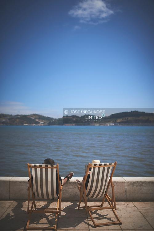 A senior couple sit over Tajo River in Belem, Portugal