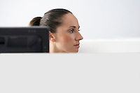 Female office worker sitting behind monitor in office cubicle portrait