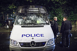 © Licensed to London News Pictures . 08/08/2011 . London , UK . A police van with smashed windscreen in Brixton during a 2nd night of rioting and looting in London , which followed a protest against the police shooting of Mark Duggan in Tottenham . Photo credit : Joel Goodman/LNP