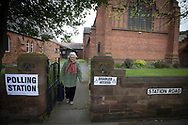 A voter leaving a polling station in Hoylake, Wirral after casting her vote at the 2015 UK General Election. She was voting in the marginal Wirral West constituency, held since the 2010 election by Esther McVey MP for the Conservative Party. Voters went to the polls across the UK on 7th May to elect 659 member of parliament.
