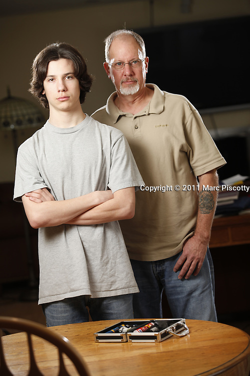 """SHOT 2/5/11 12:10:04 PM - Michael Enright and his 14 year-old son Hunter, who has Type 1 diabetes pose for a portrait at their Golden, Co. home one weekend. Michael is president of AAA Service Plumbing, Heating and Electric in Arvada and insures some 60 employees and their families through his company. He is pragmatic about the healthcare debate and doesn't believe there should ever be any lifetime cap on benefits and added, """"there seems to be a lot of other countries doing it (healthcare) better than we are here. We're definitely not getting our money's worth out of it right now."""" Hunter is a freshman at Golden High School and discovered he had diabetes when he was 11 years old. (Photo by Marc Piscotty / © 2011)"""