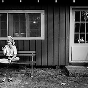 High School girls camp counselor Christina Reagan facetimes with a friend while on a bench outside a cabin at Interlochen Center for the Arts in Interlochen, Michigan.