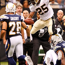 August 27, 2010; New Orleans, LA, USA; New Orleans Saints running back Reggie Bush (25) leaps over San Diego Chargers safety Eric Weddle (32) abd linebacker Brandon Lang (57) during the second quarter of a preseason game at the Louisiana Superdome. Mandatory Credit: Derick E. Hingle