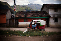 A motortaxi drives past a home of similar color in Acul, a model village, in Guatemala, on March 31, 2012. During the height of the civil war, the Guatemalan army burned the original village and built a new one designed to isolate civilians from the guerrillas, in the Ixil Triangle, Guatemala.