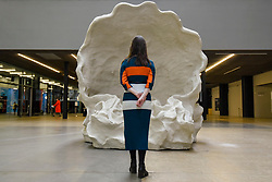 """© Licensed to London News Pictures. 30/09/2019. LONDON, UK. A staff member poses at the entrance to """"Fons Americanus"""" by Kara Walker, which has been unveiled as this year's Hyundai Commission at Tate Modern.  The work is a monumental 13 metre-high fountain presenting the origin story of the African diaspora and includes sculptural figures derived from an array of historical, literary and cultural sources.  The work, also inspired by the Victoria Memorial outside Buckingham Palace, is on display 2 October to 5 April 2020.  Photo credit: Stephen Chung/LNP"""
